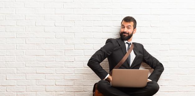 Biznesmen z jego laptopa siedząc na podłodze, trzymając ręce skrzyżowane