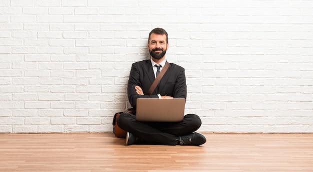 Biznesmen z jego laptopa siedzi na podłodze, trzymając ręce skrzyżowane w pozycji czołowej