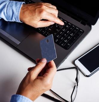 Biznesmen z kartą kredytową w ręku pracuje na komputerze. pomysł na biznes