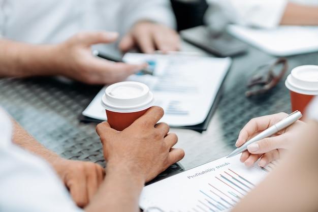 Biznesmen z kawą na wynos omawiający dokument finansowy
