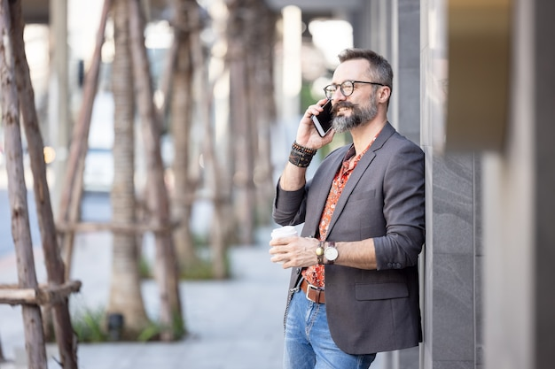 Biznesmen z kawą używać telefonu komórkowego