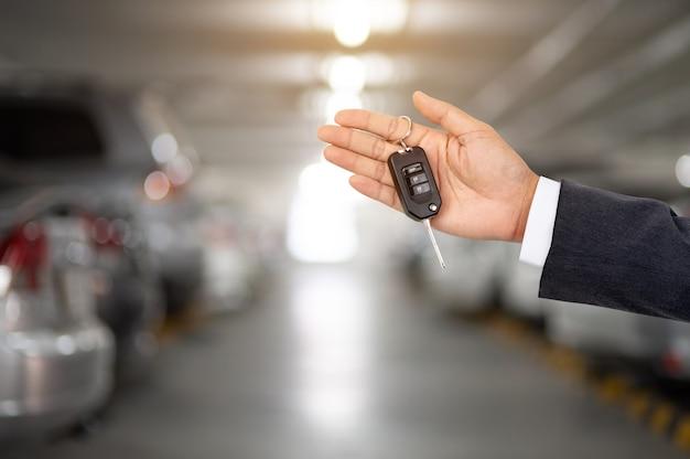 Biznesmen z kluczyki do samochodu z tyłu parkingu