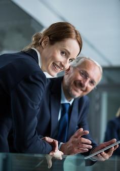 Biznesmen z kolegą używa cyfrową pastylkę