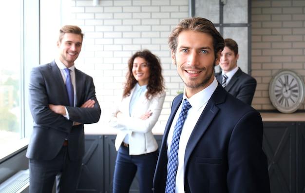 Biznesmen z kolegami w tle w biurze