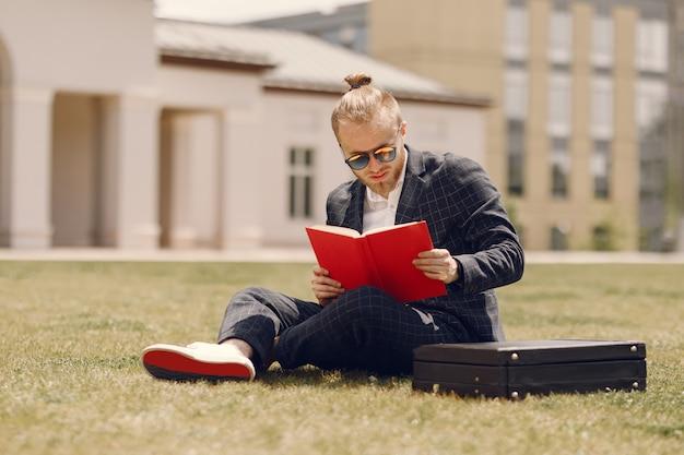 Biznesmen z książką siedzi w mieście latem
