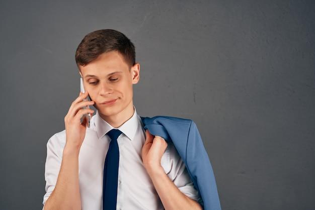 Biznesmen z kurtką na ramieniu rozmawia przez kierownika biura telefonu. zdjęcie wysokiej jakości