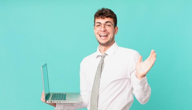 Biznesmen z laptopem czuje się szczęśliwy, podekscytowany, zaskoczony lub zszokowany, uśmiechnięty i zdumiony czymś niewiarygodnym