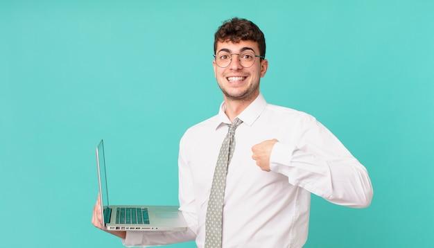 Biznesmen z laptopem czuje się szczęśliwy, zaskoczony i dumny, wskazując na siebie z podekscytowanym, zdumionym spojrzeniem