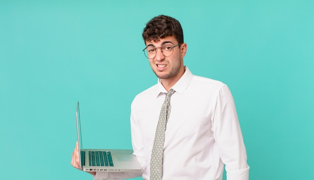 Biznesmen z laptopem czuje się zakłopotany i zdezorientowany, z tępym, oszołomionym wyrazem twarzy, patrzącym na coś nieoczekiwanego