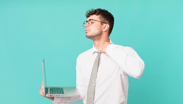 Biznesmen z laptopem czuje się zestresowany, niespokojny, zmęczony i sfrustrowany, ciągnie za koszulkę, wygląda na sfrustrowanego problemem