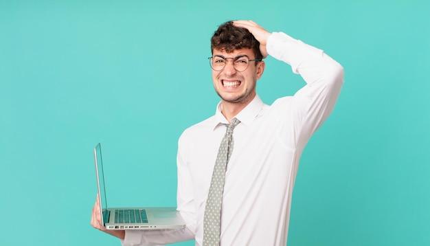 Biznesmen z laptopem czuje się zestresowany, zmartwiony, niespokojny lub przestraszony, z rękami na głowie, panikujący z powodu błędu