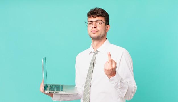 Biznesmen z laptopem czuje się zły, zirytowany, buntowniczy i agresywny, machając środkowym palcem, walczący