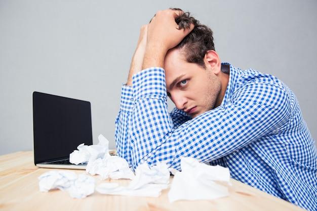 Biznesmen z laptopem i zmiętymi papierami