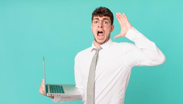 Biznesmen z laptopem krzyczy z rękami w górze, czuje się wściekły, sfrustrowany, zestresowany i zdenerwowany