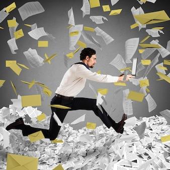 Biznesmen z laptopem ucieka od papierkowej roboty i biurokracji