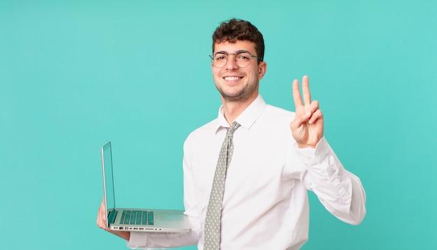 Biznesmen z laptopem uśmiecha się i wygląda przyjaźnie, pokazując cyfrę dwa lub sekundę z ręką do przodu, odliczając w dół