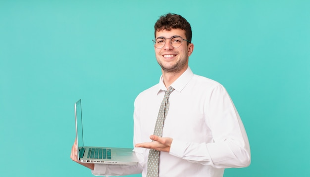 Biznesmen z laptopem uśmiecha się radośnie, czuje się szczęśliwy i pokazuje koncepcję w przestrzeni kopii z dłonią