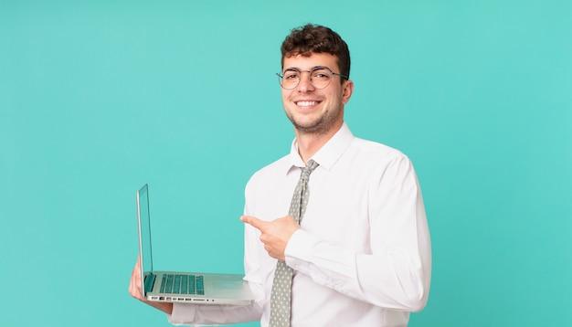 Biznesmen z laptopem uśmiecha się radośnie, czuje się szczęśliwy i wskazuje na bok i do góry, pokazując obiekt w przestrzeni kopii