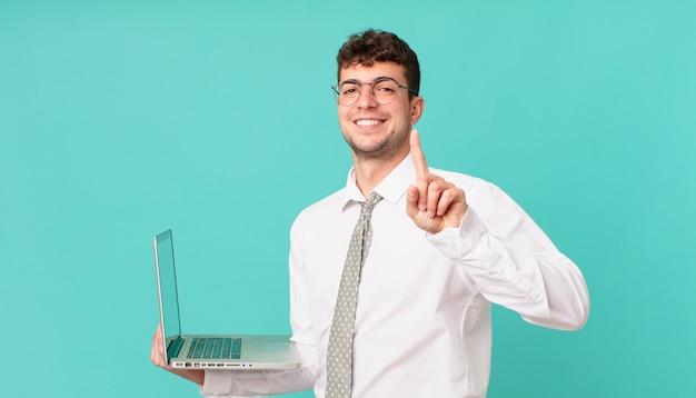 Biznesmen z laptopem uśmiechający się dumnie i pewnie robiąc triumfalną pozę numer jeden, czując się jak lider