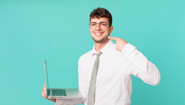 Biznesmen z laptopem uśmiechający się pewnie wskazując na własny szeroki uśmiech, pozytywna, zrelaksowana, usatysfakcjonowana postawa