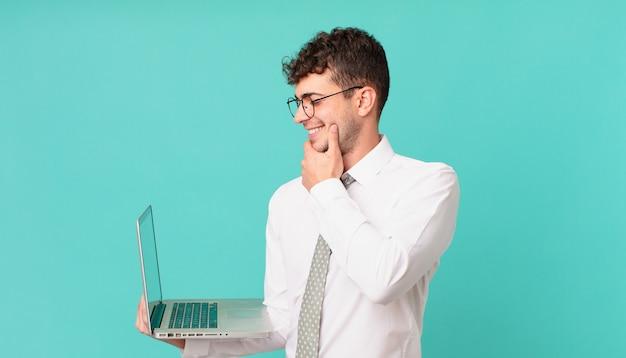 Biznesmen z laptopem uśmiechający się ze szczęśliwym, pewnym siebie wyrazem twarzy z ręką na brodzie, zastanawiający się i patrzący w bok