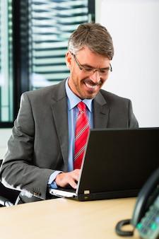 Biznesmen z laptopem w jego biurze firmy