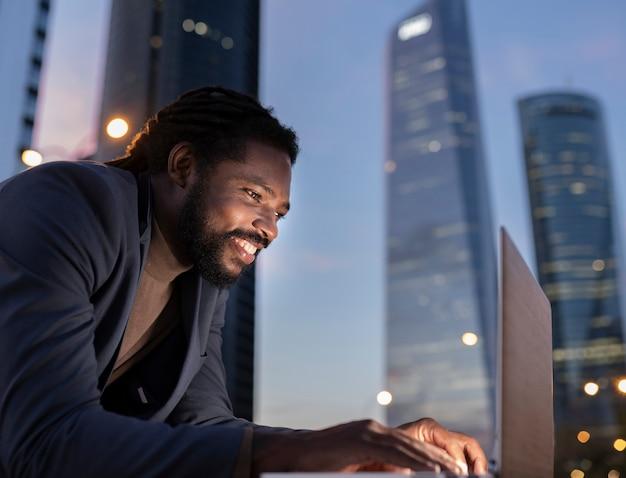 Biznesmen z laptopem w nocnych budynkach
