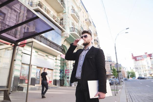 Biznesmen z laptopem w ręku stoi na tle architektury miasta