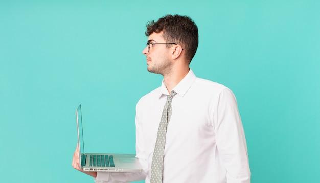 Biznesmen z laptopem w widoku profilu, który chce skopiować przestrzeń do przodu, myśląc, wyobrażając sobie lub marząc na jawie
