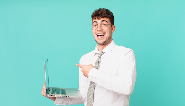 Biznesmen z laptopem wygląda na podekscytowanego i zdziwionego, wskazując na bok i w górę, aby skopiować przestrzeń