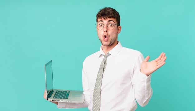 Biznesmen z laptopem wyglądający na zaskoczonego i zszokowanego, z opuszczoną szczęką, trzymający przedmiot z otwartą dłonią z boku
