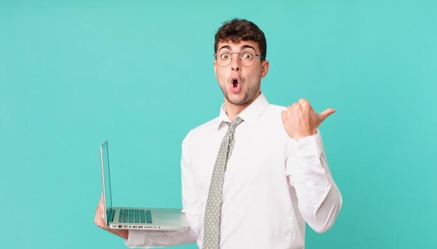 """Biznesmen z laptopem wyglądający na zdziwionego z niedowierzaniem, wskazując na przedmiot z boku i mówiący """"wow, niewiarygodne"""""""