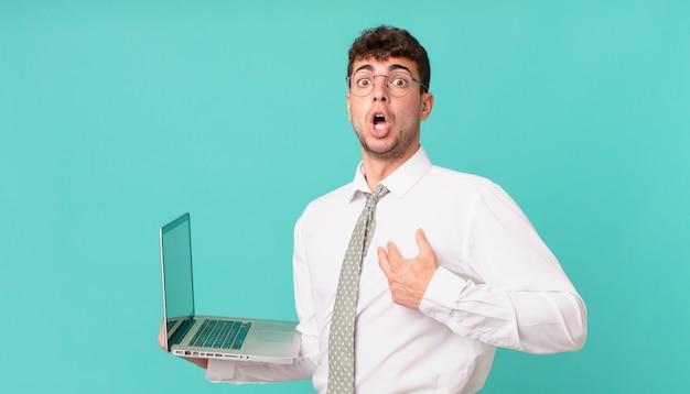Biznesmen z laptopem wyglądający na zszokowanego i zdziwionego z szeroko otwartymi ustami, wskazujący na siebie