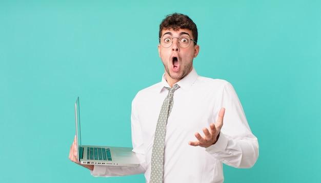 Biznesmen z laptopem z otwartymi ustami i zdumiony, zszokowany i zdumiony niewiarygodną niespodzianką