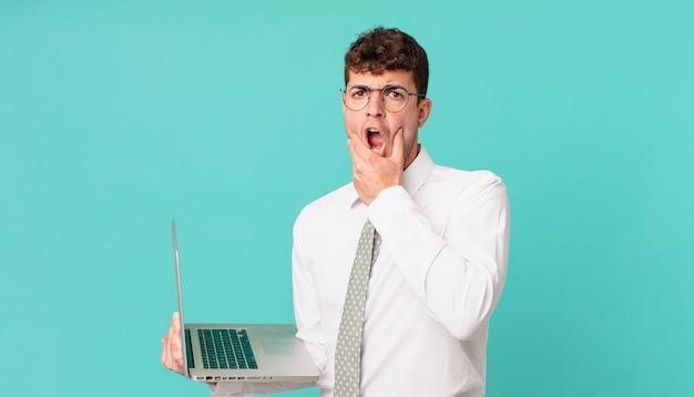 Biznesmen z laptopem z szeroko otwartymi ustami i oczami i ręką na brodzie, czując się nieprzyjemnie zszokowany, mówiąc co lub wow