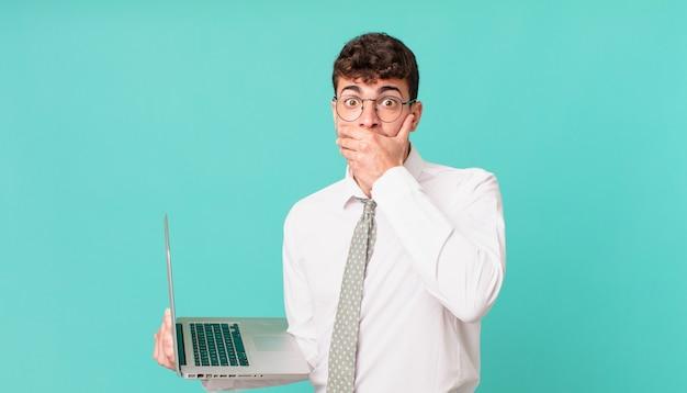 """Biznesmen z laptopem zakrywający usta dłońmi ze zszokowanym, zaskoczonym wyrazem twarzy, dochowujący tajemnicy lub mówiącym """"ups"""""""