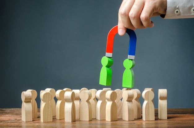 Biznesmen z magnesem wyciąga z tłumu zielone postacie ludzi. rekrutacja nowych pracowników