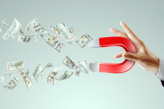 Biznesmen z magnesem zbiera dolary, przyciąga pieniądze. prawidłowa strategia biznesowa, dochód pasywny, ponad zysk.