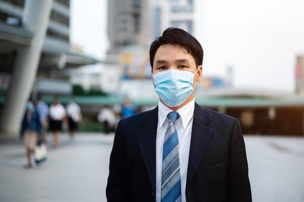 Biznesmen z maską medyczną podczas pandemii koronawirusa w mieście