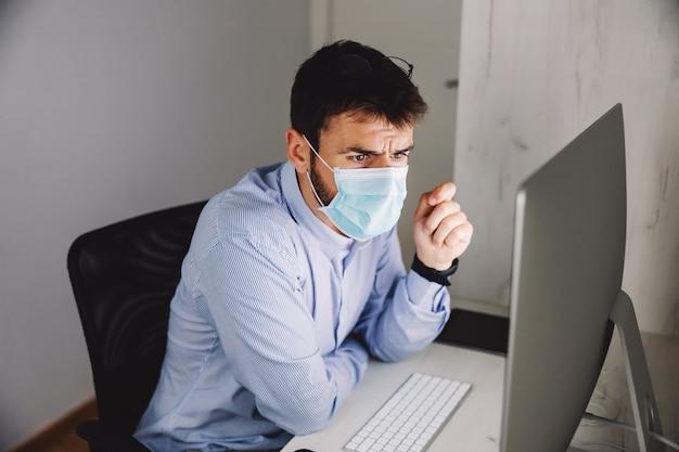 Biznesmen z maską na siedzeniu w swoim biurze podczas wirusa koronowego i patrząc na komputer