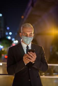 Biznesmen z maską ochronną na twarz w mieście w nocy przy użyciu telefonu