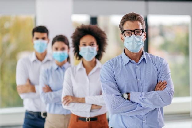 Biznesmen z maską stoi w firmie z założonymi rękami, a za nim jego koledzy z założonymi rękami i maskami na twarz.