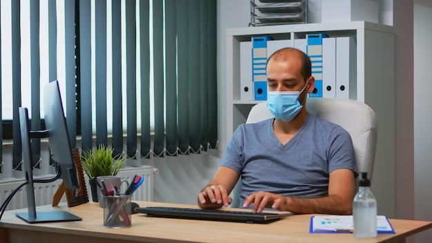 Biznesmen z maski medycznej ochrony pisania na komputerze w pokoju biurowym. przedsiębiorca w nowym, normalnym, osobistym miejscu pracy, pisanie korporacyjne na klawiaturze komputera, patrząc na pulpit