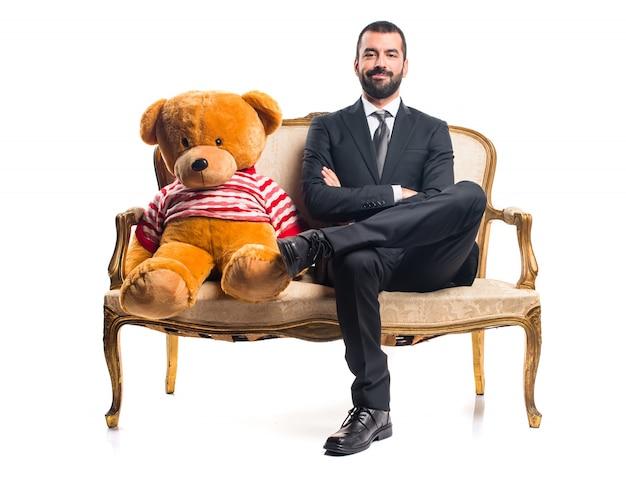 Biznesmen z misiem siedzi na rocznika fotel