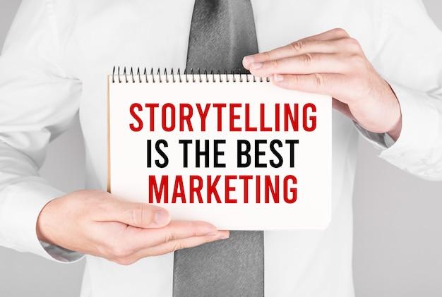 Biznesmen z notatnikiem z tekstem opowiadanie historii to najlepszy marketing