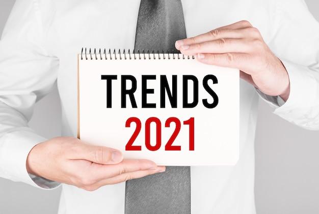 Biznesmen z notatnikiem z tekstem trendy 2021