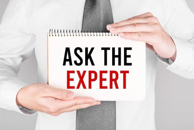 Biznesmen z notatnikiem z tekstem zapytaj eksperta