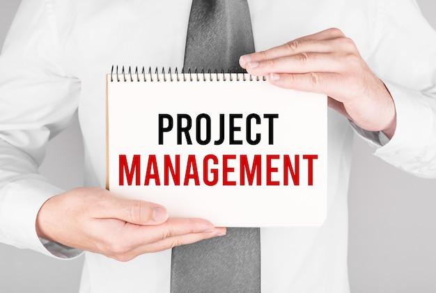 Biznesmen z notatnikiem z tekstem zarządzanie projektami