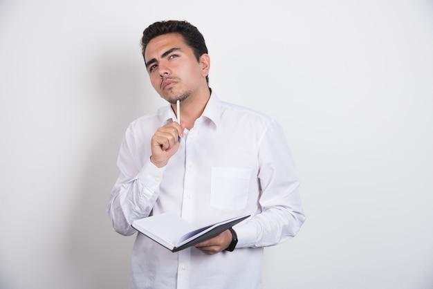 Biznesmen z notebooka myśli ciężko na białym tle.