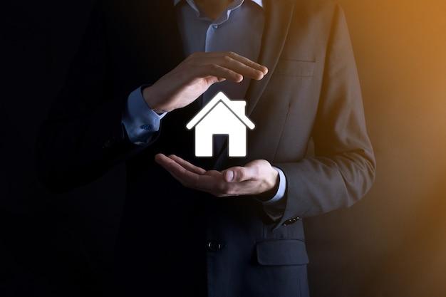 Biznesmen z ochronnym gestem postawa stojąca ręka trzyma dom ikona słowo napis.